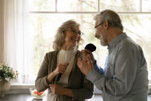 Overjoyed Mature Man And Woman Singing Into Kitchenware, Holding Beater And Ladle, Having Fun In Kitchen, Enjoying Leisure Time, Happy Laughing Elderly Wife And Husband Dancing, Listening To Music