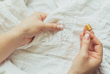 Woman Sews A Dress. Hands With A Needle And Thimble Close Up