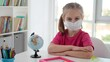 Little girl in protective mask sitting at school desk during quarantine
