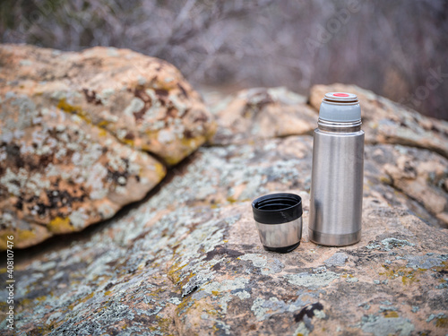 small steel thermos bottle and hot tea on a rock during cold season hiking © MarekPhotoDesign.com