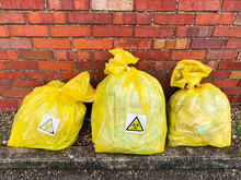 Bagged Face Masks And Rubbish Marked With Bio Hazard Symbols.