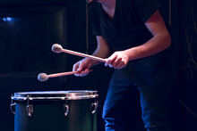 The Drummer Plays With Mallets On Floor Tom In Dark Room.