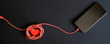 A Dark Smartphone Charged With A Red Cable And A Red Heart Lie On A Black Background. A Vital Telephone Conversation.