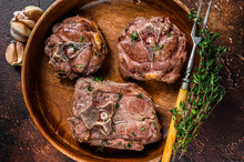 Fried Lamb Neck Meat Steaks In A Wooden Plate With Herbs. Dark Background. Top View