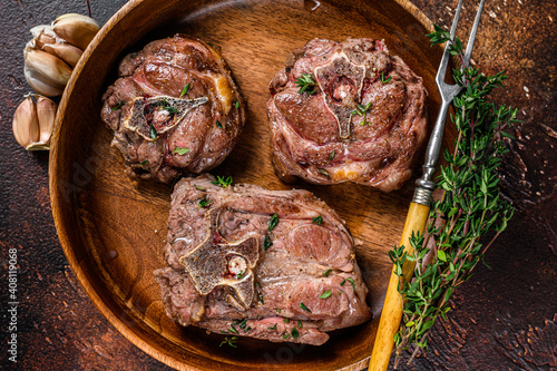 Obraz na plátně Fried lamb neck meat steaks in a wooden plate with herbs