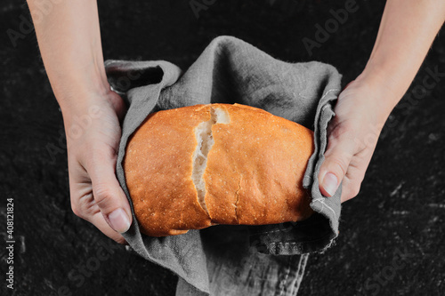Obraz na plátne Man hands cutting bread into half on dark table with tablecloth