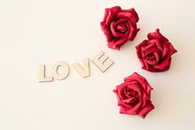 "Wooden Letters With The Inscription Of The Word ""Love"" On A White Background And Next To Three Red Roses"