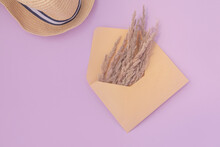 Wildflowers In An Envelope And A Straw Hat On A Pink Background. Summer Concept.
