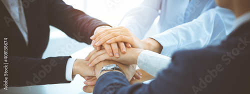 Business team showing unity with their hands together in sunny office. Group of people joining hands and representing concept of friendship, teamwork and partnership