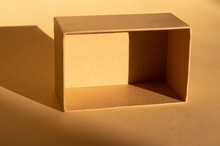 Brown Cardboard Box On Beige Background And Its Shadow