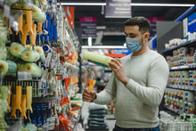 A Buyer Wearing Medical Mask Chooses A Paint Roller In A Hardware Store.