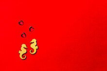 Two Lovers Wooden Seahorses With A Crystal Heart On A Red Background. A Copy Of The Space. Valentine's Day And Wedding Concept