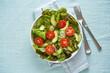 Leinwandbild Motiv Vegan salad with tomatoes, cucumbers, avocado on pastel linen tablecloth. Vegeterian mediterranean food, low calories dieting meal