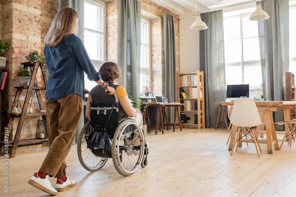 Fototapeta Rear view of young woman pushing wheelchair with her disable colleague