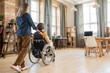 Rear view of young woman pushing wheelchair with her disable colleague