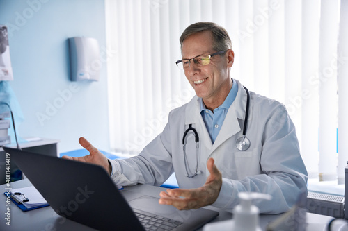 Slika na platnu Happy old male doctor physician talking, consulting patient online by webcam video call on laptop computer