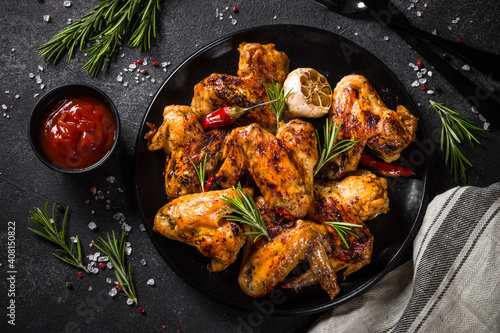 Canvas Print Grilled chicken wings with spices at black table
