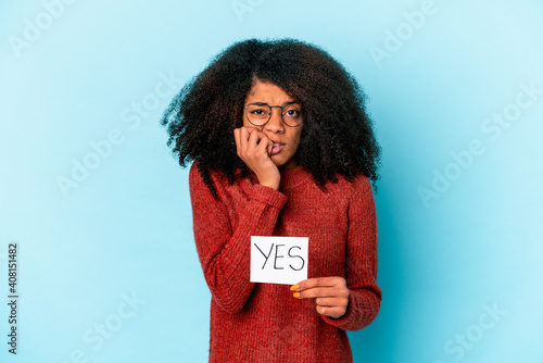 Obraz na plátne Young african american curly woman holding a yes placard biting fingernails, nervous and very anxious