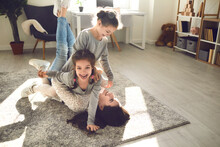 Family Enjoying Quality Time And Having Fun At Home. Young Mom And Little Kids Playing On Carpet Backlit With Sunlight. Happy Mother And Cute Carefree Children Fooling Around And Laughing On Floor Rug