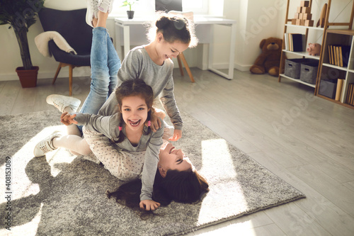 Obraz Family enjoying quality time and having fun at home. Young mom and little kids playing on carpet backlit with sunlight. Happy mother and cute carefree children fooling around and laughing on floor rug - fototapety do salonu