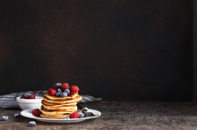 Delicious Homemade Pancakes In A Plate With Berries: Raspberries, Blueberries And Maple Syrup On A Concrete Background. With Copy Space.