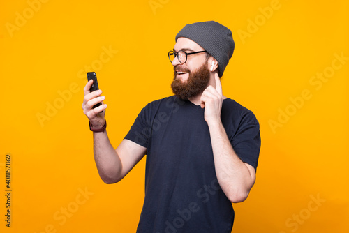 Fotomural Photo of bearded hipster man looking at smartphone and listening music at earpods