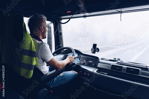 Obraz Handsome driver at the wheel of a truck at work. Work of a lorry driver. - fototapety do salonu