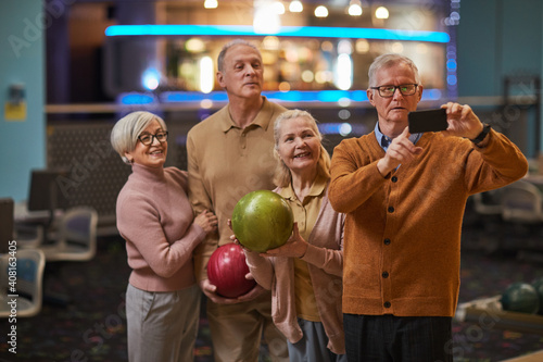 Leinwand Poster Group of senior people taking selfie photos playing bowling and enjoying active