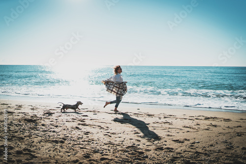 Photo Happy blonde woman running alongside the sea shore with her pet dog on a sunny day