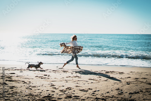 Smiling blonde woman running alongside the sea side with her pet dog on a sunny day Wallpaper Mural