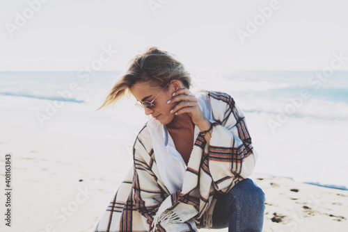 Fotografija Portrait of a blonde woman in sunglasses wearing white shirt and blue jeans sitting on haunches on the beach in a warm plaid on a sunny and windy day