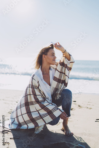 Beautiful barefoot blonde woman wearing casual outfit taking off her sunglasses while sitting on haunches at seaside on a windy sunny day Fototapeta