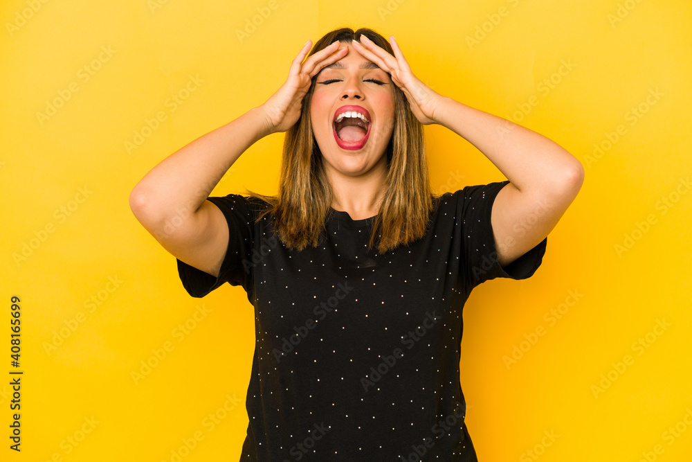 Fototapeta Young indian woman isolated on yellow background laughs joyfully keeping hands on head. Happiness concept.