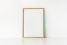 Empty Wooden Frame Stands On White Table Against Wall. Mockup Poster Frame Close Up In Home Interior.