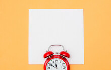 Red Alarm Clock And White Mockup Board On Yellow Background