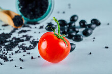 Tomatoes, A Jar Of Caviar And Black Olives On Blue Background