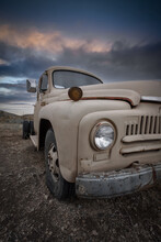 Old Abandoned Rusty Truck With Cloudy Sky Background