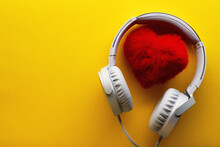 .Red Heart And White Headphones On A Yellow Background. Love Music Lifestyle Concept. Valentine's Day
