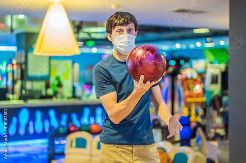 Man playing bowling with medical masks during COVID-19 coronavirus in bowling cl Fotobehang