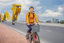 A Man Rides A Bicycle On The Dragon Bridge In Da Nang