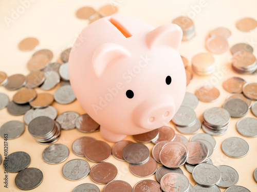Fotografia, Obraz Cute piggy bank, pink color with piles of thai baht coins on soft beige background