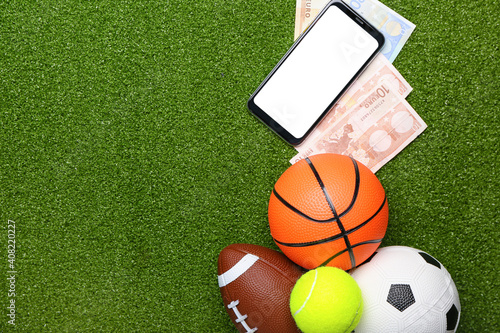 Obraz Money, mobile phone and balls on color background. Concept of sports bet - fototapety do salonu