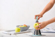 Woman Grating Apples At Table