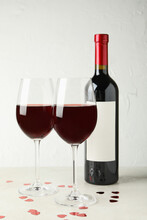 Bottle And Glasses Of Red Wine On White Textured Table