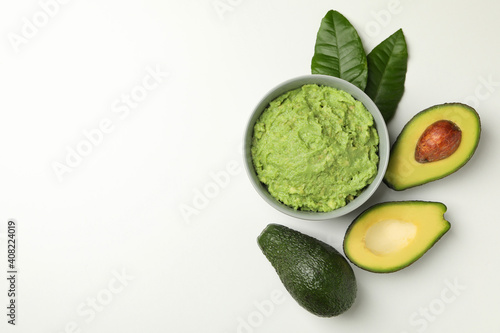 Valokuva Bowl of guacamole and avocado on white background, space for text