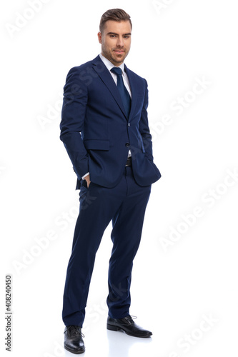 Fototapeta smiling young man in navy blue suit holding hands in pockets