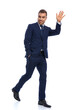 full body picture of happy businessman holding hand up and waving