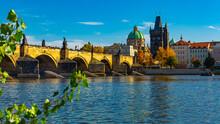 Scenic View Of Autumn Prague Cityscape And Ancient Stone Charles Bridge Across Vltava River On Sunny Day, Czech Republic
