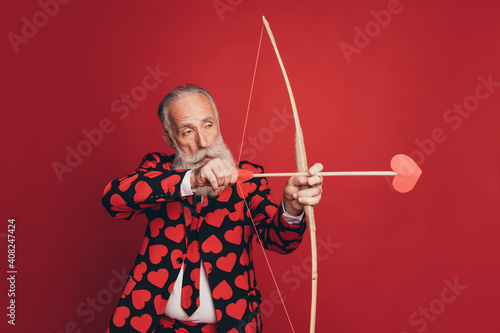 Profile photo of concentrated pensioner archer hold bow arrow aim wear heart pri Wallpaper Mural