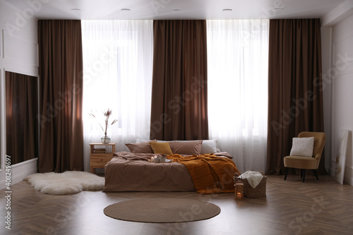 Obraz Bed with brown linens in stylish room interior - fototapety do salonu